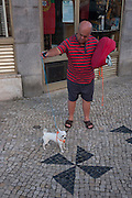 A proud pet owner shows off his precious Chihuahua on the street near Alameda, in Lisbon, Portugal.