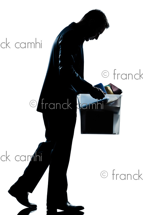 one caucasian man walking  full length fired carrying heavy box silhouette in studio isolated white background