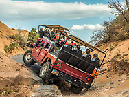 A Hummer lifts a tire climbing during a 4x4 Hummer tour on the Hell's Revenge Trail in the Sandflats Recreation Area near Moab, Utah.