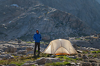 Adult male wearing blue down jacket enjoying the view at backcountry camp in Indian Basin, Bridger Wilderness,  Wind River Range Wyoming