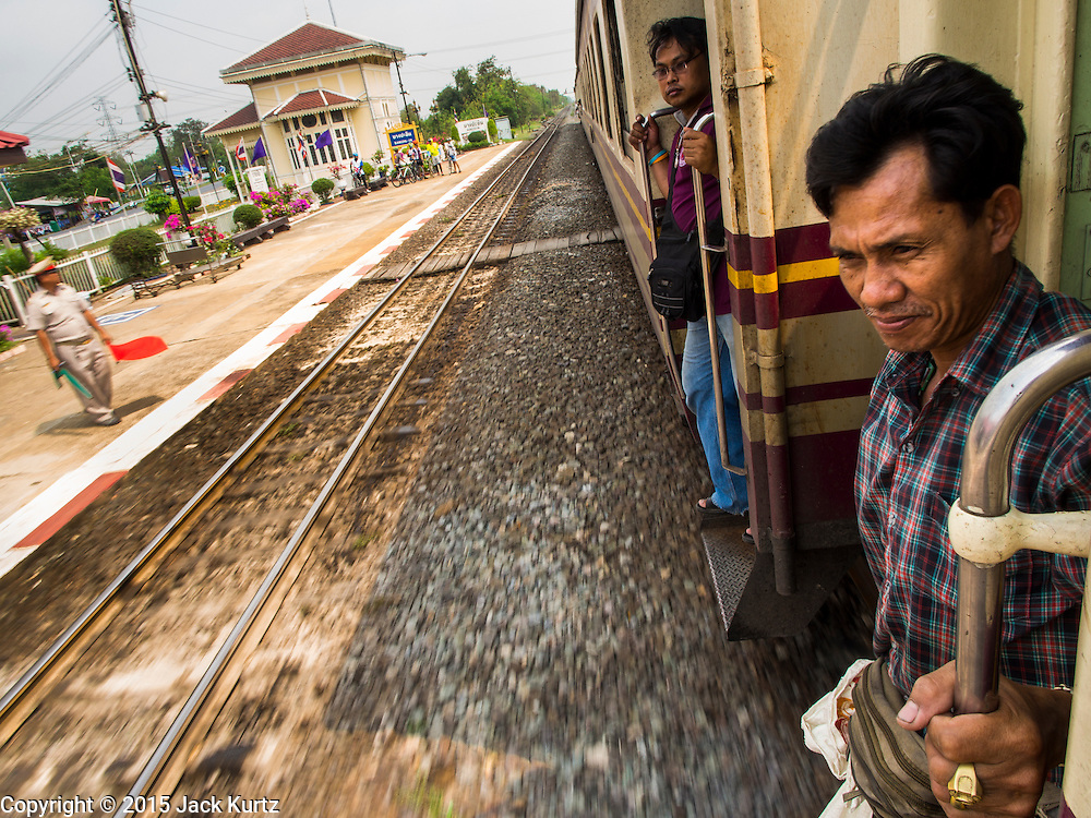 19 MARCH 2015 - AYUTTHAYA, AYUTTHAYA, THAILAND:  A man prepares to step off the Ayutthaya to Bangkok third class train as the train pulls into Bang Pa In station near Ayutthaya. The train line from Bangkok to Ayutthaya was the first rail built in Thailand and was opened in 1892. The State Railways of Thailand (SRT), established in 1890, operates 4,043 kilometers of meter gauge track that reaches most parts of Thailand. Much of the track and many of the trains are poorly maintained and trains frequently run late. Accidents and mishaps are also commonplace. Successive governments, including the current military government, have promised to upgrade rail services. The military government has signed contracts with China to upgrade rail lines and bring high speed rail to Thailand. Japan has also expressed an interest in working on the Thai train system. Third class train travel is very inexpensive. Many lines are free for Thai citizens and even lines that aren't free are only a few Baht. Many third class tickets are under the equivalent of a dollar. Third class cars are not air-conditioned.   PHOTO BY JACK KURTZ