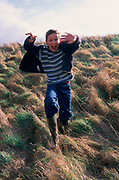 A913TF Boy running down a grass slope and jumping at the camera