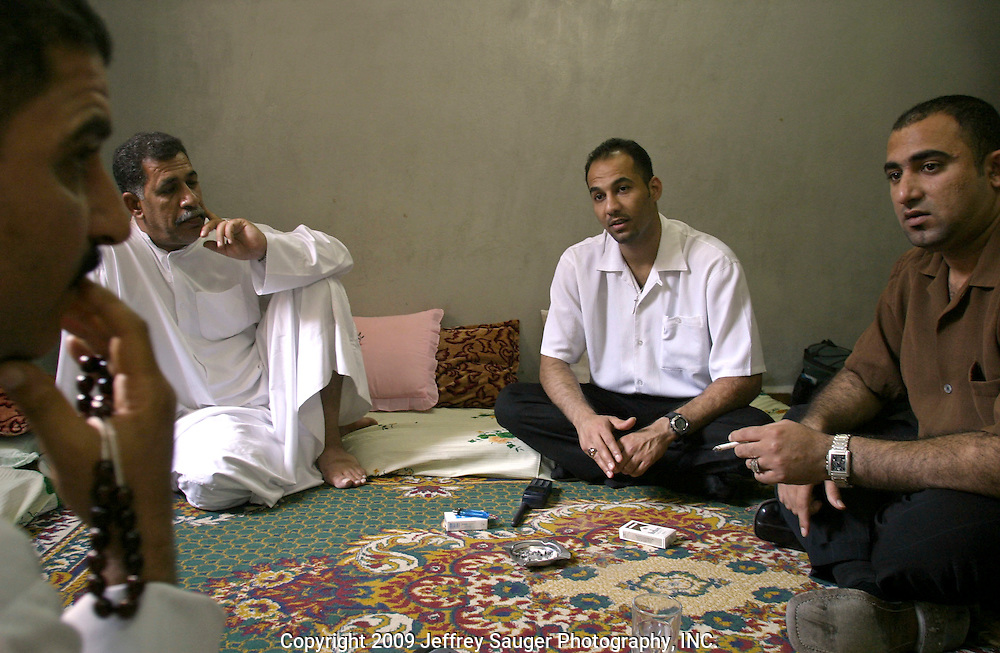 Haider Al-Jubury, far right, talks with his cousin Akel Al-Kahfiji, far left and Uncle Muhsen Al-Khafiji, second from left, who had arrived earlier in the day from Samawa, Iraq, at their relative's apartment in the Iraqi area in Damascus, Syria, Friday, July 18, 2003. Emad Al-kasid, second from right, and Al-Jubury, have been planning a trip home to Iraq over the last year. They've been meeting with family, friends and contacts for the past week gathering information on the best way to travel to and from Iraq. ..Today was the first time Al-Jubury has seen his cousin and uncle in 13 years since he fled Samawa after fighting in the uprising against Saddam Hussein in 1991. His brother Hussein was the first Shiite to take up arms against the Baath Party in Samawa and was killed.