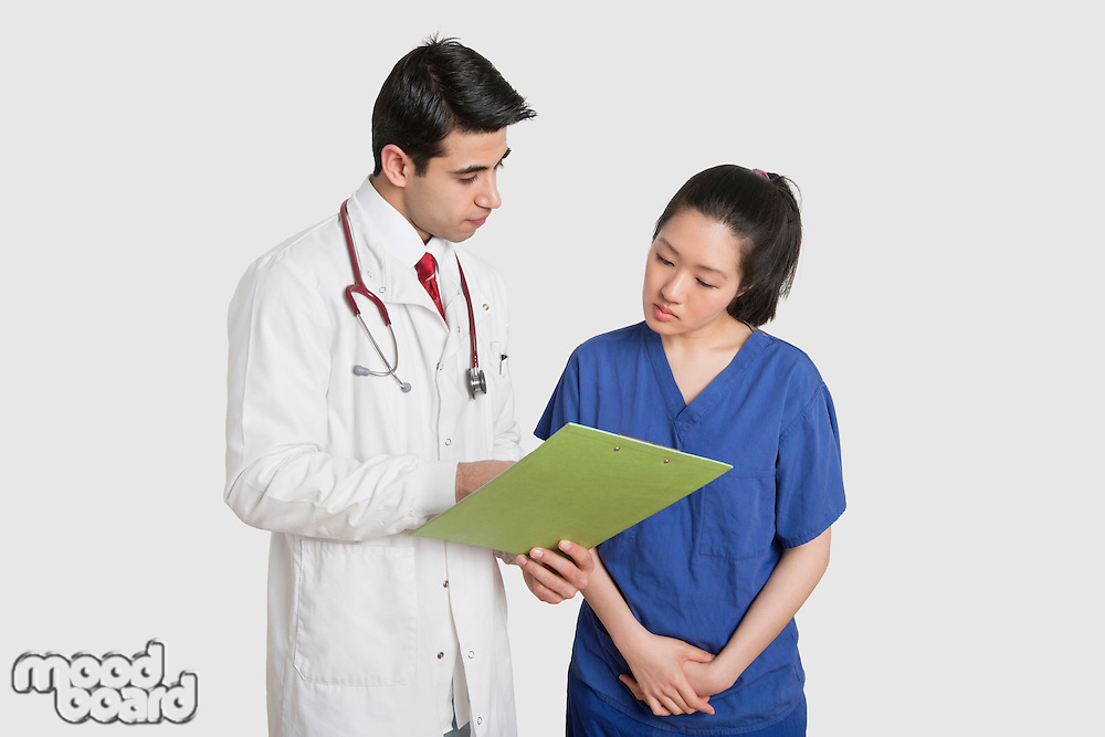 Doctor discussing medical report with female nurse over gray background