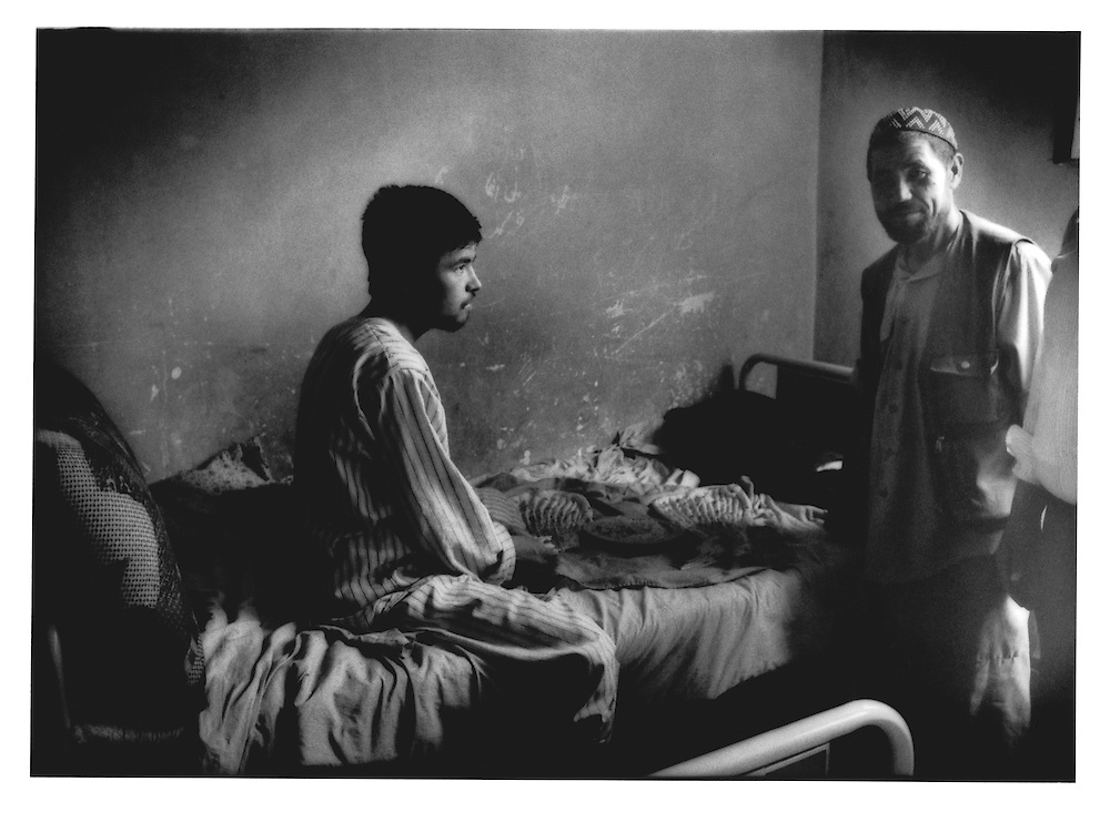 Psychiatric patient stares out past his father who has come to Kabul with him during his stay at Kabul's only gov?t run mental hospital, Psychiatric and Drug Dependency Hospital, Kabul, Afghanistan.