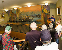 Christine Hadsel of Curtains Without Borders explains the restoration process to the crowd gathered for the Opening Reception for the Moulton Opera House curtain at Laconia Library Wednesday evening.  (Karen Bobotas/for the Laconia Daily Sun)