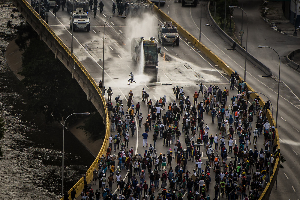 CARACAS, VENEZUELA - MAY 27, 2017:  National guard soldiers fire a water cannon from an armored vehicle, along with tear gas, rubber bullets and buckshot at anti-government protesters who had taken over the Francisco Fajardo highway - the main highway that runs through Caracas. The streets of Caracas and other cities across Venezuela have been filled with tens of thousands of demonstrators for nearly 100 days of massive protests, held since April 1st. Protesters are enraged at the government for becoming an increasingly repressive, authoritarian regime that has delayed elections, used armed government loyalist to threaten dissidents, called for the Constitution to be re-written to favor them, jailed and tortured protesters and members of the political opposition, and whose corruption and failed economic policy has caused the current economic crisis that has led to widespread food and medicine shortages across the country.  Independent local media report nearly 100 people have been killed during protests and protest-related riots and looting.  The government currently only officially reports 75 deaths.  Over 2,000 people have been injured, and over 3,000 protesters have been detained by authorities.  PHOTO: Meridith Kohut