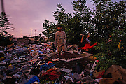 Boys play on top of a garbage pile behind their home in Nova Gazela.