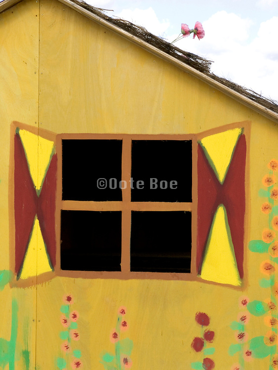 close up of the window of a funny painted little house on the beach Holland