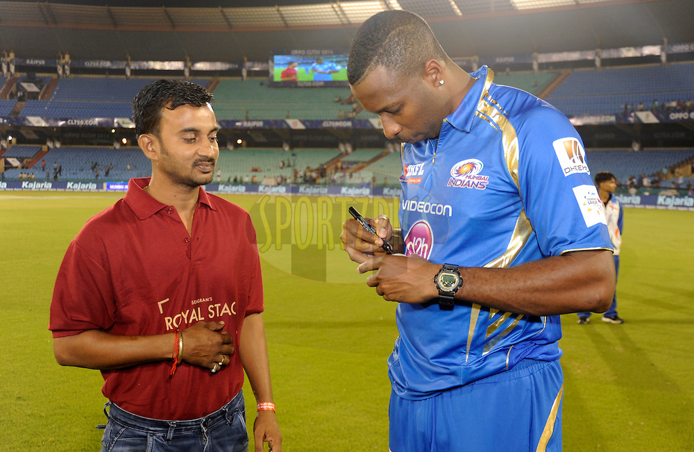 Kieron Pollard captain of Mumbai Indians  signs the ball for Royal Stag fan of the match during the qualifier 4 match of the Oppo Champions League Twenty20 between the Mumbai Indians and the Southern Express held at the Chhattisgarh International Cricket Stadium, Raipur, India on the 14th September 2014<br /> <br /> Photo by:  Pal Pillai / Sportzpics/ CLT20<br /> <br /> <br /> Image use is subject to the terms and conditions as laid out by the BCCI/ CLT20.  The terms and conditions can be downloaded here:<br /> <br /> http://sportzpics.photoshelter.com/gallery/CLT20-Image-Terms-and-Conditions-2014/G0000IfNJn535VPU/C0000QhhKadWcjYs