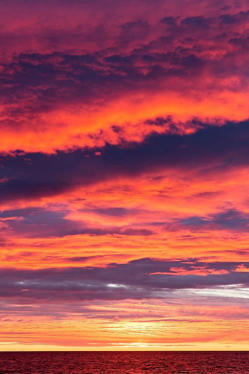 Canada, Manitoba, Rising sun lights dramatic clouds above Hudson Bay at Hubbart Point