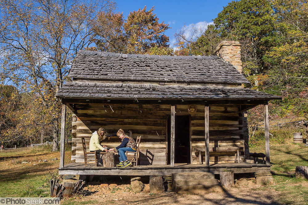 A mother and son play a game of checkers on the porch of an old cabin at Humpback Rocks Mountain Farm, a restored 1890s farmstead open to the public at Milepost 5.8 on the Blue Ridge Parkway, in Virginia, in the Blue Ridge Mountains (a subset of the Appalachian Mountains), USA. In summer, costumed interpreters demonstrate 1890s southern Appalachian mountain life. European settlers of the Appalachian Mountains forged a living from abundant native materials: hickory, chestnut, and oak trees provided nuts for food, logs for building, and tannin for curing hides; and the rocks were used as foundations, chimneys and stone fences. This farm was originally a Land Grant tract dispensed by the Commonwealth of Virginia to induce pioneers to settle; and later it became known as the William J. Carter Farm.