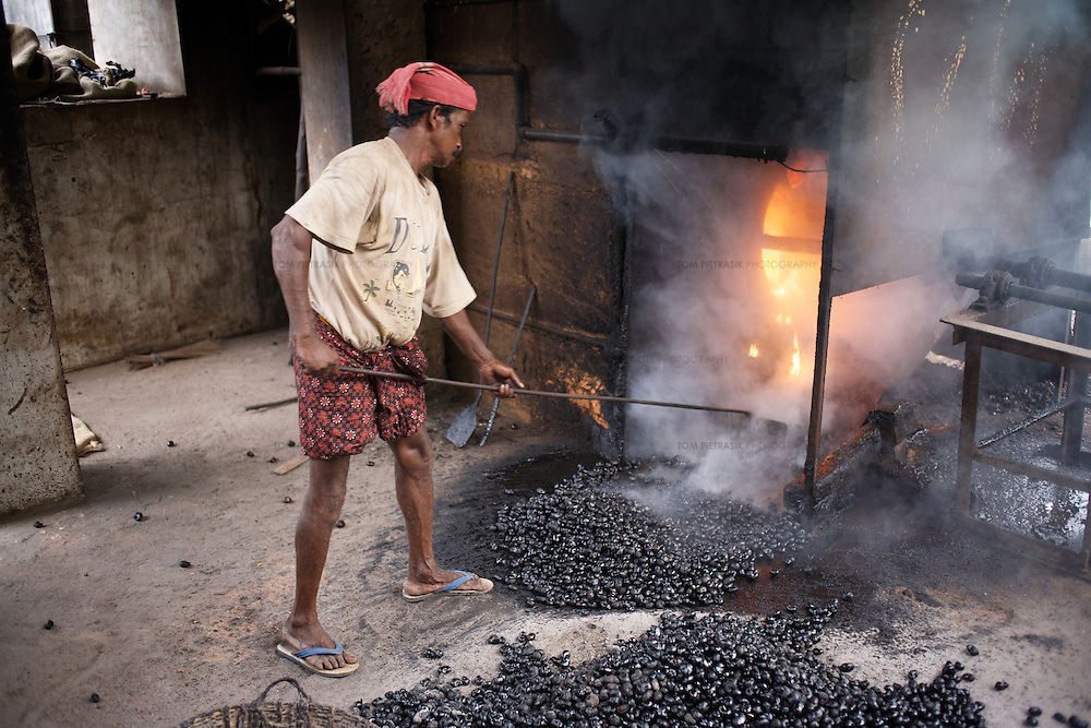 A worker roasts cashew nuts to prepare them for shelling at Sai Cashew Factory in Kanyakumari District. The minimum 180 foot regulation for chimneys roasting cashews are often flouted...The women workers workers at this factory earn between Rs.8-13 per kilo of shelled nut they process. Workers process between 8-10kg of cashew nut per day. Hazards include burning from the acidic oil released from the cashew shell when it is cracked. Workers protect their hands with improvised gloves and a coating of ash. The work is highly repetitive and many workers suffer back-pain and arthritis. Some of the women workers have reported damage to the uterus. The discarded shell of the nut is packed and sold as a component in the production of a termite-resistant chemical used to treat wood. Unlike workers in neighbouring Kerala government factories, workers in Tamil Nadu receive no pension contribution from their employers...In Tamil Nadu's Kanyakumari District alone there are 580 cashew processing factories. In Tamil Nadu state there are a total of 760. In Kanyakumari District 175,000 workers are employed in the cashew industry...The expanding global market for cashew nuts has a direct effect on the livelihoods of women workers in the Indian cashew processing industry. The power imbalance between intensely competing producers and relatively few buyers in the global market place gives large retailers, the supermarkets, the upper hand over their supply chains. Supermarkets are increasingly able to dictate the terms on which business is done and how the cashew is produced, as well as to capture most of the revenue generated along the chain. For Indian workers who process the cashew nuts such work, while essential for survival, does not provide enough income to raise households out of poverty. The increasing informalisation of employment in the sector creates insecure and hazardous working conditions. International trade too often fails to provide the kind of economic growth which will