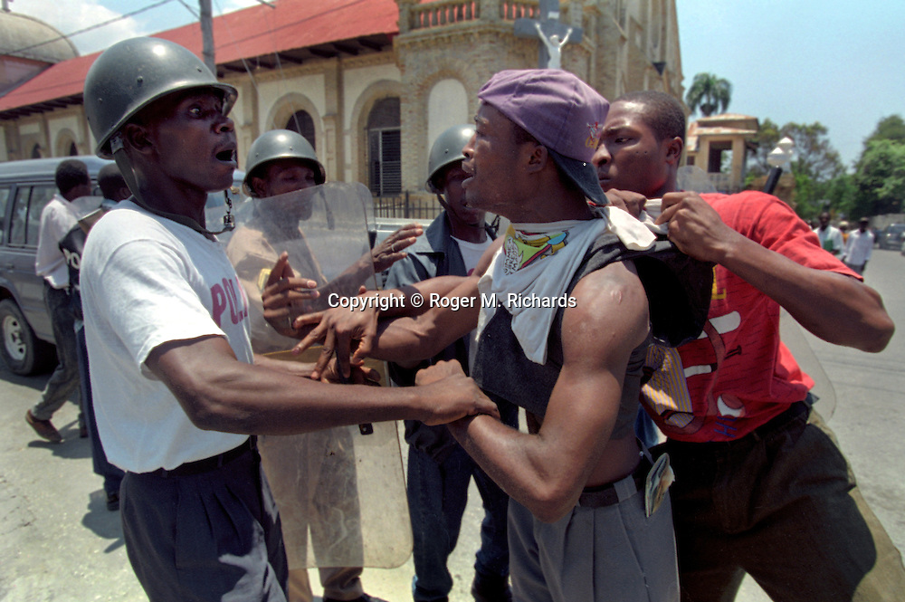 A Haitian policemen arrests a rioter during street violence in Port-au-Prince, Haiti, May 1995. (Photo by Roger M. Richards)