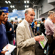 October 31, 2013 - New York, NY : Alan Ruben, center, treasurer of the Central Park Track Club and longtime marathoner -- he has run 26 New York City Marathons -- picks up his bib number and runner packet at the Jacob K. Javits Center on Thursday afternoon during the New York City Marathon Expo. CREDIT: Karsten Moran for The New York Times