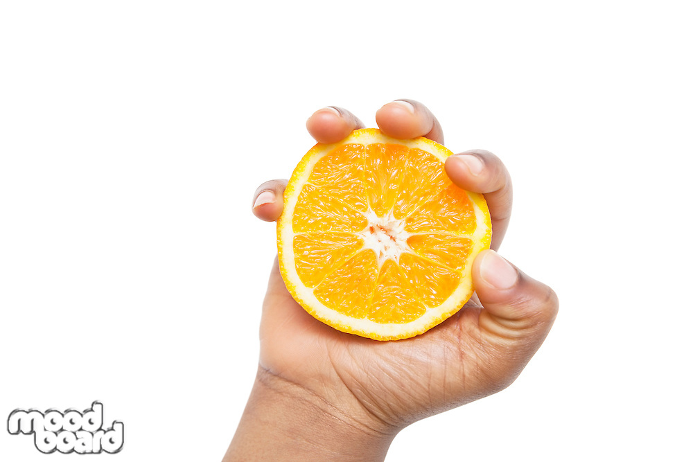 Cropped shot of a hand holding sliced pulpy orange against white background