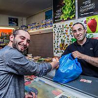 Nederland, Amsterdam, 23 juli 2016.<br />We volgen de Syrische jongen Ibrahim Najjar in de Spaarndammerbuurt in zijn zoektocht naar de ingredienten voor het Syrische kipgerecht Mskhan, een Syrisch ovengerecht met kip, citroen en ui.<br />Hij heeft zijn buren uitgenodigd bij hem te komen eten.<br />Op de foto: Ibrahim doet boodschappen bij kruidenier Kardeslar Market in de Spaarndammerstraat.<br /><br /><br /><br /><br />Foto: Jean-Pierre Jans