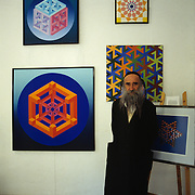 Famed Kabbala geometric artist Yaakov Kaszmacher poses with some of his paintings in his gallery in Tsfat (Safed), Israel.
