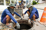 24 AUGUST 2013 - BANGKOK, THAILAND:      Prisoners wait on the street while one of their fellow prisoners work in a sewer below the street. A work gang from a prison near Bangkok clean the sewers along Soi 22 Sukhumvit.   PHOTO BY JACK KURTZ