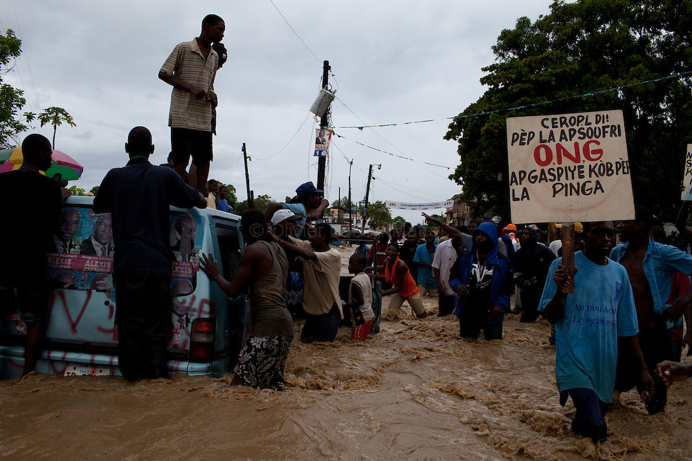 "After hurricane Tomas went through Haiti, the city of Leogane has been totally flooded by the heavy rain and the overflow of the river Roullorne.///Haitians demonstrate in the the muddy water, in a street of Leogane during hurricane Tomas, to protest against the lack of help from the local authorities and the NGOs.///A man (R) holds a placard saying in Creole : ""The people is suffering but the NGOs are wasting people's money. Be Careful."""