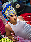 "30 JANUARY 2016 - NONTHABURI, NONTHABURI, THAILAND: A performer relaxes backstage during a ""likay"" show at Wat Bua Khwan in Nonthaburi, north of Bangkok. Likay is a form of popular folk theatre that includes exposition, singing and dancing in Thailand. It uses a combination of extravagant costumes and minimally equipped stages. Intentionally vague storylines means performances rely on actors' skills of improvisation. Like better the known Chinese Opera, which it resembles, Likay is performed mostly at temple fairs and privately sponsored events, especially in rural areas. Likay operas are televised and there is a market for bootleg likay videos and live performance of likay is becoming more rare.     PHOTO BY JACK KURTZ"