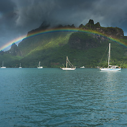 Sail boats lie under the most intense and beaufitul rainbow I have ever sees. Cook's bay, Moorea, French-Polynesia.