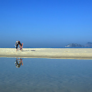 A beach scene on Ipanema beach, as a jogger runs past a pool of water left behind by the receding tide, Rio de Janeiro,  Brazil. 9th July 2010. Photo Tim Clayton..