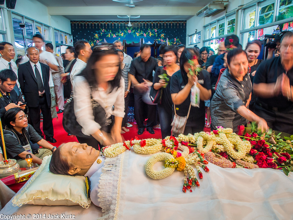 12 OCTOBER 2104 - BANG BUA THONG, NONTHABURI, THAILAND: People rush forward to place flowers on the body of Apiwan Wiriyachai, at his funeral rites at Wat Bang Phai in Bang Bua Thong, a Bangkok suburb, Sunday. Apiwan was a prominent Red Shirt leader, member of the Pheu Thai Party of former Prime Minister Yingluck Shinawatra, and a member of the Thai parliament. The military government that deposed the elected government in May, 2014, charged Apiwan with Lese Majeste for allegedly insulting the Thai Monarchy. Rather than face the charges, Apiwan fled Thailand to the Philippines. He died of a lung infection in the Philippines on Oct. 6. The military government gave his family permission to bring him back to Thailand for the funeral. He will be cremated later in October. The first day of the funeral rites Sunday drew tens of thousands of Red Shirts and their supporters, in the first Red Shirt gathering since the coup.    PHOTO BY JACK KURTZ
