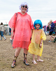 © Licensed to London News Pictures. 12/06/2015. Isle of Wight, UK.  Festival goers - a mother and her young daughter - at Isle of Wight Festival 2015 wearing brightly coloured anoraks to shelter from the light rain the morning of  Friday Day 2 of the festival.  Yesterday the weather was hot and Sunny.  Today rain is forecast.  This years festival include headline artists the Prodigy, Blur and Fleetwood Mac.  Photo credit : Richard Isaac/LNP