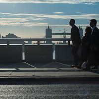 London, UK - 1 September 2014: cummuters cross London Bridge as the sun rises behind Tower Bridge
