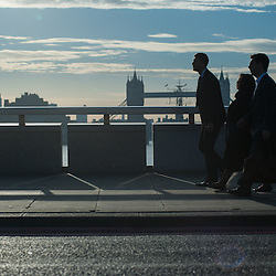 London, UK - 1 September 2014: cummuters cross London Bridge as the sun rises behind Tower Bridge
