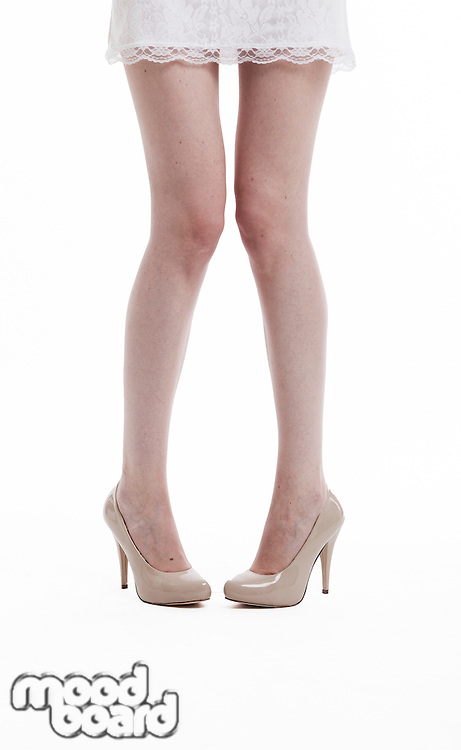 Low section of young woman in dress wearing high heels over white background