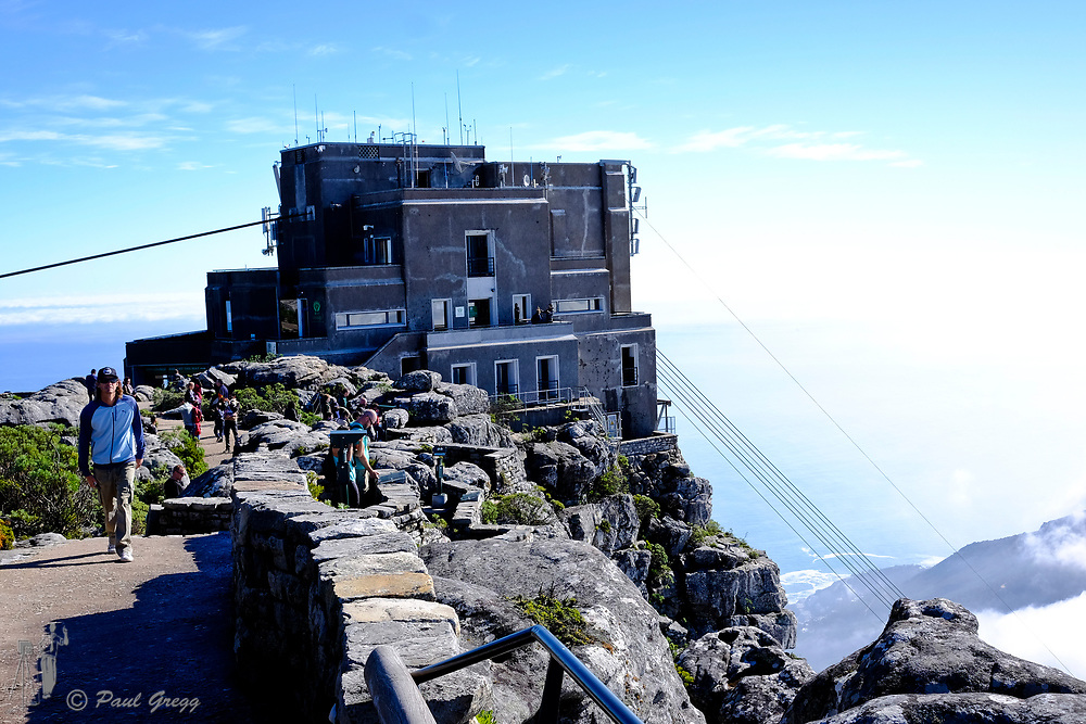 Cape Town, South Africa. Above the clouds. Tourists enjoy the view from the top of Table Mountain with a blanket of clouds below. The upper station of the cable car is in the background.