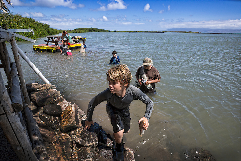 Alex Johnston, 12, takes mullet he caught at the Keawanui Fishpond on Molokai.  The fish was cleaned and eaten as part of dinner that night.
