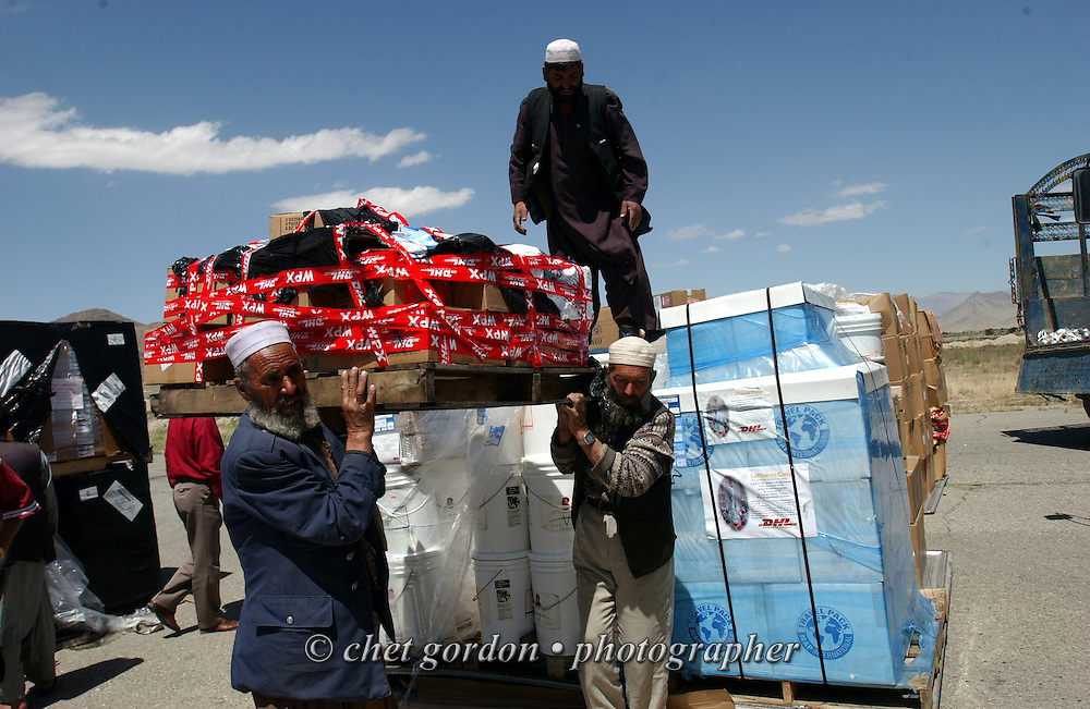 "Afghan men carry a pallet of humanitarian aide supplies after it was unloaded from an Antonov-12, a Russian cargo aircraft, at the Kabul airport on Thursday afternoon, May 23, 2002. The Geshundheit Instititute, founded by Dr. Hunter ""Patch"" Adams, Lufthansa Cargo, and DHL Worldwide Express collaborated to ship medicines, food and orthopedic supplies to the Indira Ghandi Children's Hospital, clinics and orphanages in Kabul. The German NGO (Non Governmental Organization) Hammer Forum supervised the distribution of the donated supplies from various non-profit organizations in the U.S. and The Netherlands."