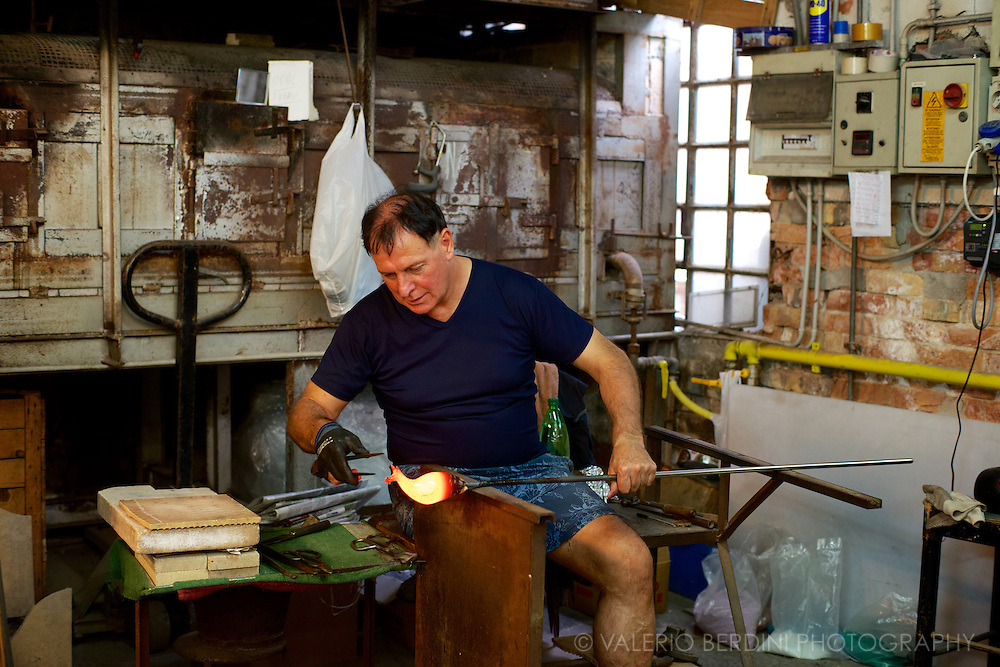 A glassmaker in the process of pulling a horse out of a incandescent bead. The whole process takes few seconds and a pair of tweezers.