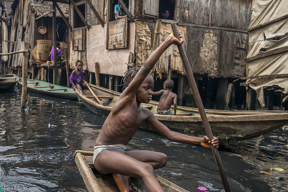 A girl paddles her canoe through the dirty waters of Makoko