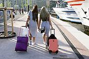 Nederland, the Netherlands, Amsterdam, 20-4-2018 Twee jonge vrouwlijke toeristen, mannen, lopen met hun koffers vanaf het centraal station naar het westerdok  . Foto: Flip Franssen