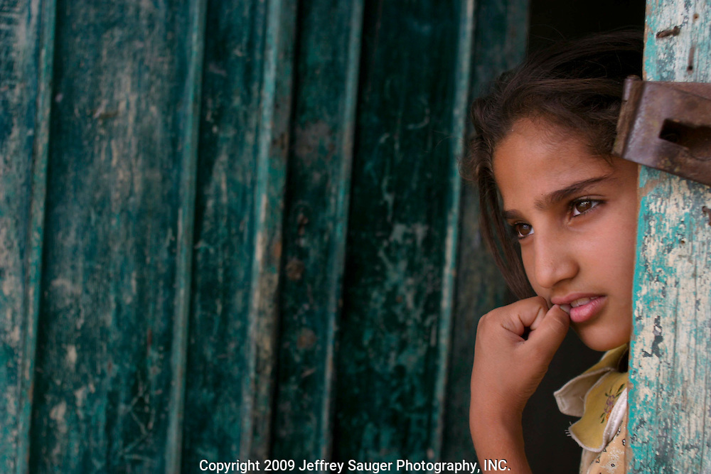 Zanab Abdallah, 10, Kawther Al-Kasid's neice, peeks from behind a door during the Al-kasid family's Istikbal, or homecoming, in their home village Suq ash Shuyukh on the outskirts of Nasiriyah, Iraq, July 30, 2003. The celebration lasts three days with different tribal chiefs, family members and friends coming and going. ..The Al-Kasid family fled Iraq after the Gulf War and their part in the uprising against Saddam Hussein in 1991, spent 3 years in Rafha, Saudi Arabia and finally settled in Dearborn, MI. The family hasn't been home to Iraq in 13 years.