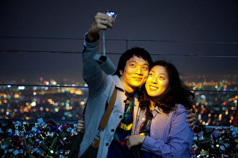Seoul/South Korea, Republic of Korea, KOR, 30.04.2009: Young couple photographing each other during an evening mood at the lowest observation deck of the N Seoul Tower surrounded by lockers. N Seoul Tower is a communication tower located in Seoul, South Korea. Built in 1969, and opened to the public in 1980, the tower measures 236.7 m (777 ft) in height (from the base) and tops out at 479.7 m (1,574 ft) above sea level.