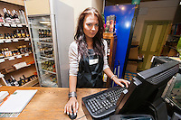 Portrait of saleswoman using computer at cash counter in supermarket
