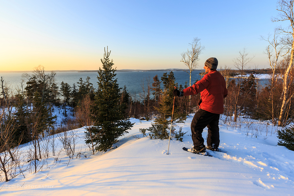 A man on snowshoes takes in the view of the mouth of the Penobscot River as seen from the Witherle Woods Preserve in Castine, Maine in winter.