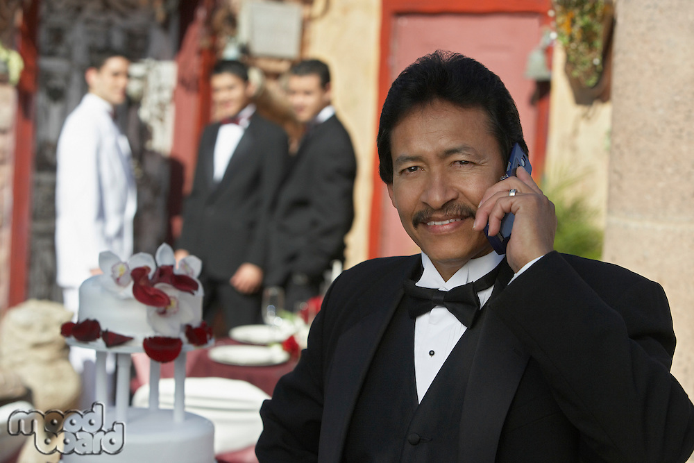 Man in tuxedo at wedding, using mobile phone