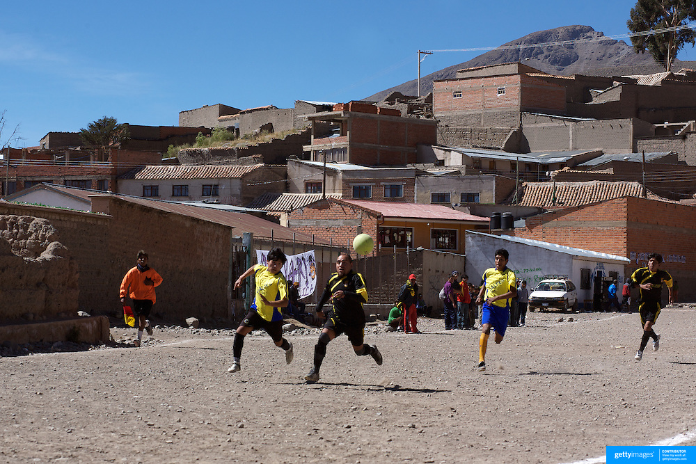 'Attitude at Altitude' Football in Potosi, Bolivia'..Players from the Calvario and Galpes S.C. (yellow) teams play during the Liga Deportiva San Cristobal cup final on the stone and gravel surface high in the hills over Potosi, Calvario won the match 3-1. Potosi, Bolivia 9th May 2010..'Attitude at Altitude' Football in Potosi, Bolivia'..The Calvario players greet the final whistle with joyous celebration, high fives and bear hugs the players are sprayed with local Potosina beer after a monumental 3-1 victory over arch rivals Galpes S.C. in the Liga Deportiva San Cristobal. The Cup Final, high in the hills over Potosi. Bolivia, is a scene familiar to many small local football leagues around the world, only this time the game isn't played on grass but a rock hard earth pitch amongst gravel and boulders and white lines that are as straight as a witches nose, The hard surface resembles the earth from Cerro Rico the huge mountain that overlooks the town. .. Sitting at 4,090M (13,420 Feet) above sea level the small mining community of Potosi, Bolivia is one of the highest cities in the world by elevation and sits 'sky high' in the hills of the land locked nation. ..Overlooking the city is the infamous mountain, Cerro Rico (rich mountain), a mountain conceived to be made of silver ore. It was the major supplier of silver for the spanish empire and has been mined since 1546, according to records 45,000 tons of pure silver were mined from Cerro Rico between 1556 and 1783, 9000 tons of which went to the Spanish Monarchy. The mountain produced fabulous wealth and became one of the largest and wealthiest cities in Latin America. The Extraordinary riches of Potosi were featured in Maguel de Cervantes famous novel 'Don Quixote'. One theory holds that the mint mark of Potosi, the letters PTSI superimposed on one another is the origin of the dollar sign...Today mainly zinc, lead, tin and small quantities of silver are extracted from the mine by over 100 co operatives and private mi
