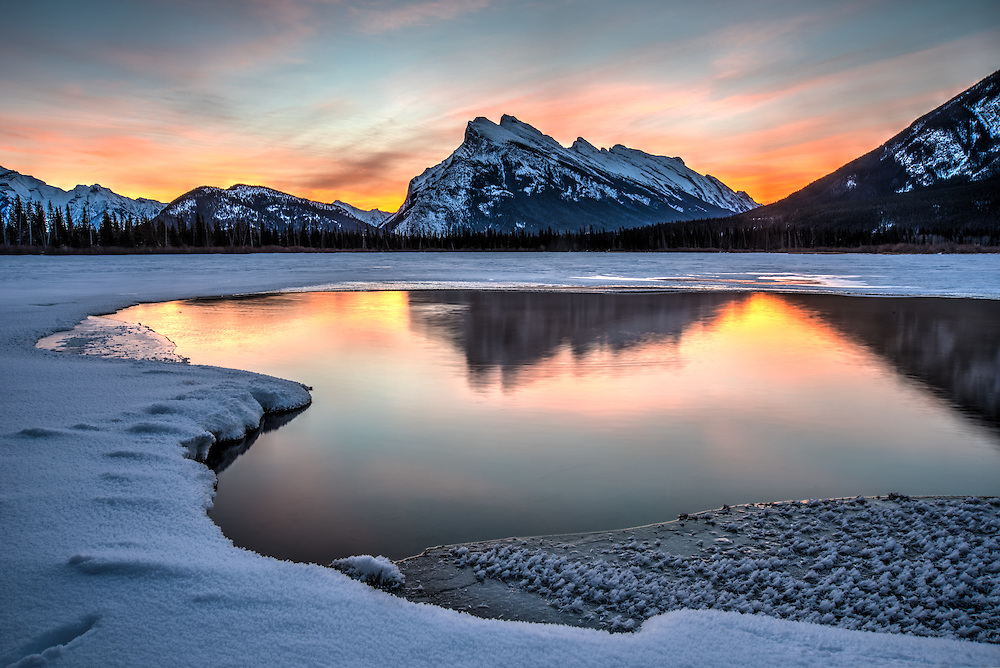 This insanely colorful sunrise creates the perfect backlight to Mount Rundle in Banff National Park in Alberta, Canada on a bitterly cold winter morning. The only thing that makes this better is the whole scene reflected in the open water of a natural hot spring that keeps this part of the Vermillion Lakes from freezing.