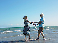 Senior couple holding hands on beach while dancing side view