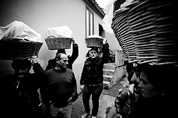 """Verbicaro/Calabria/Italy 20-03-08 - Ritual of the """"Battenti"""". The Procession of the bread. On the night of Holy Thursday Verbicaro stages the traditional rite of Battenti, which dates back to 1473. Initially characterized by """"the rite of the first blood"""", which means the protagonists beat their legs vigorously with their hands until they become red. Then, with a tool cork """"cardillo"""" which has embedded pieces of glass, they start to beat themselves and the first blood flows. As the blood flows, a man carrying a bottle to his lips, blows wine into the wounds...When everyone has his legs covered with blood, they start to run with hands crossed on the chest. Three times they circle the old town stopping in front of churches. They leave as a group but it is not a procession, each runner has their own route and the streets may differ. The event takes place between Thursday  and Friday  (between midnight and 02.00). At 4.00 (approx.) in the morning there is a solemn procession with living statues and paintings."""