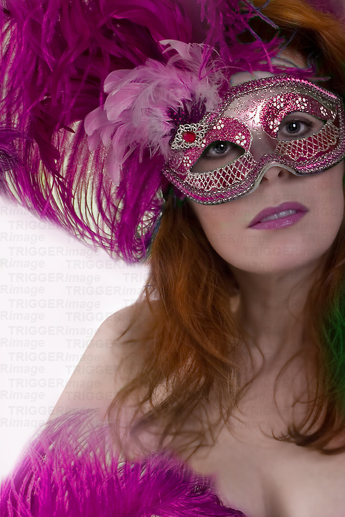 woman wearing pink feathery mask looking at camera