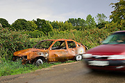 Car passes a burnt-out wreck by the roadside, Oxfordshire, United Kingdom