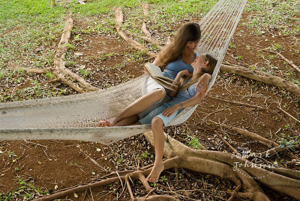 Mother & daughter reading a book in hammock together